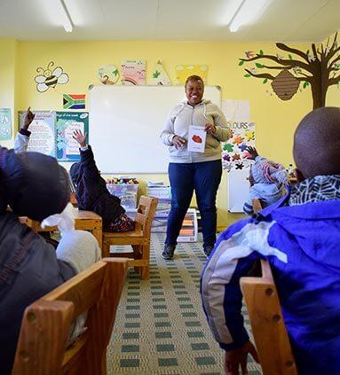 Teacher in classroom, teaching enthusiastic African orphaned children