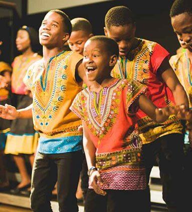 African boy singing in choir dressed in traditional attire