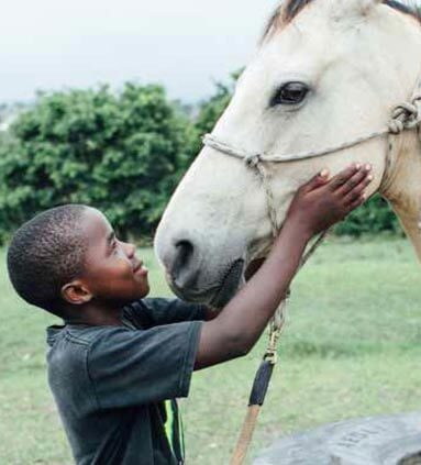 African Boy Patting Horse